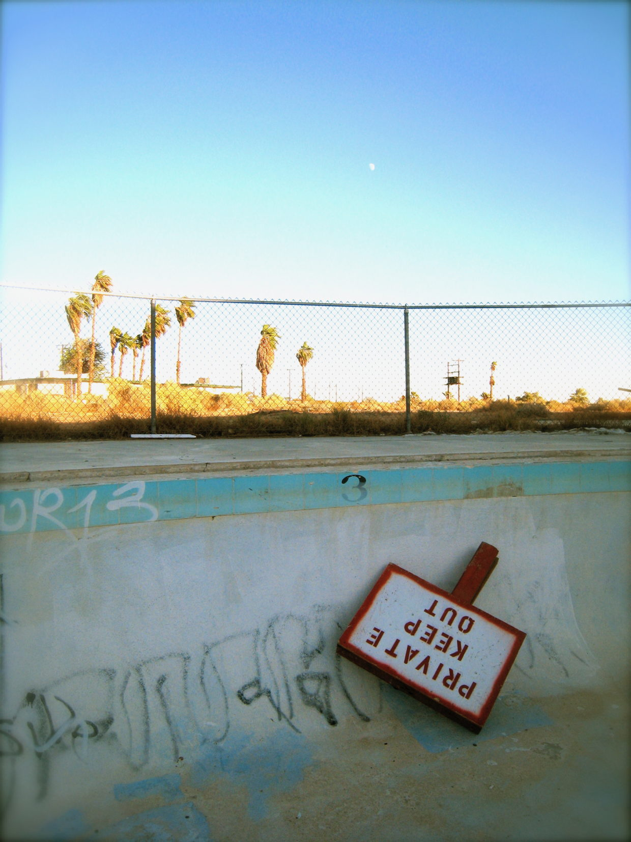 a Keep Out sign in an empty pool
